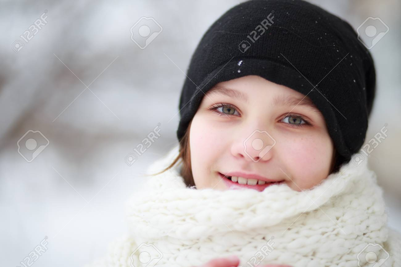 6f6de401efe35e beautiful teenage girl in a black jacket and hat, with a white scarf, is  holding two red Christmas-tree toys in her hands. A child dresses a  Christmas tree ...