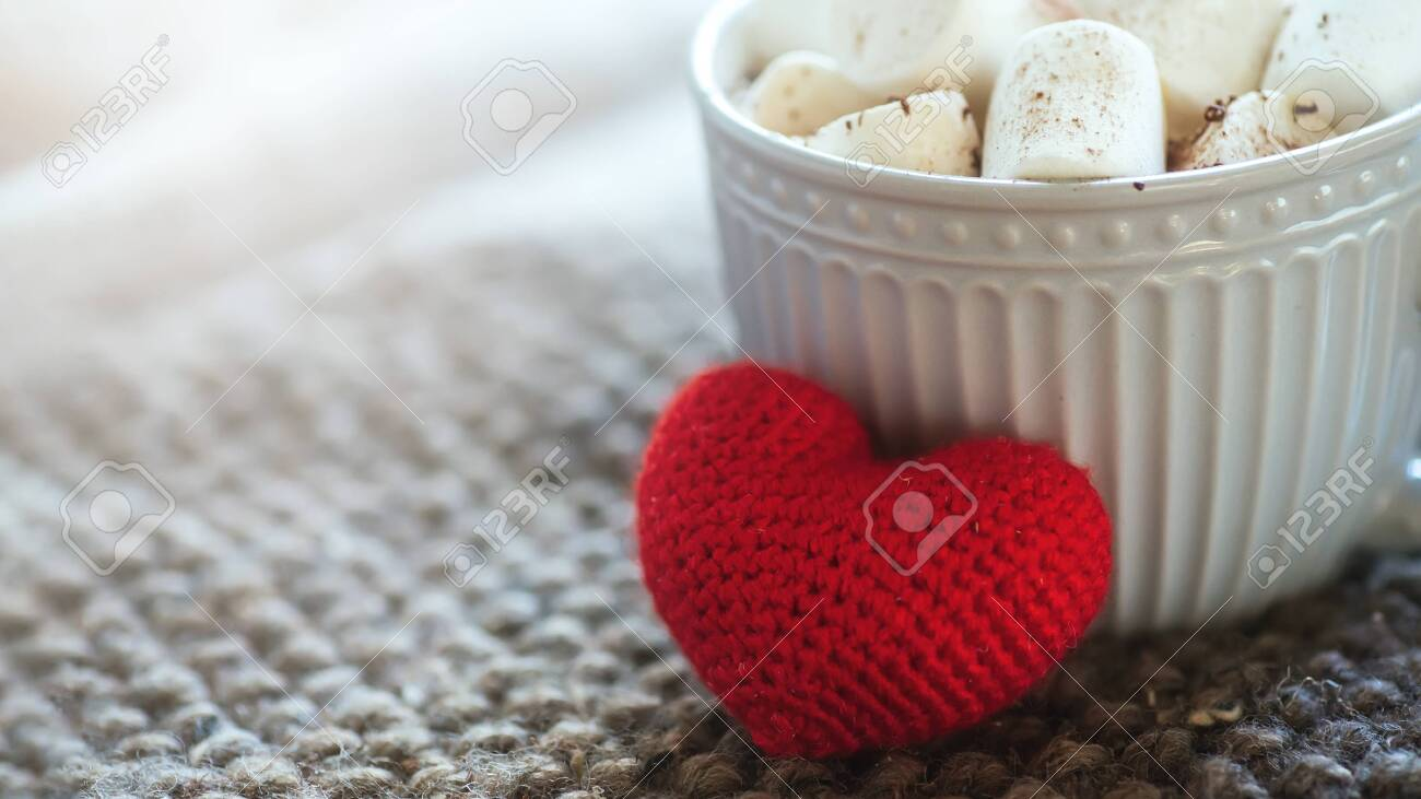 Background with gray cup with marshmallows and red heart on knitted napkin. warm drink with grey scarf.. Valentines day concept, mug cup of coffee - 135842647