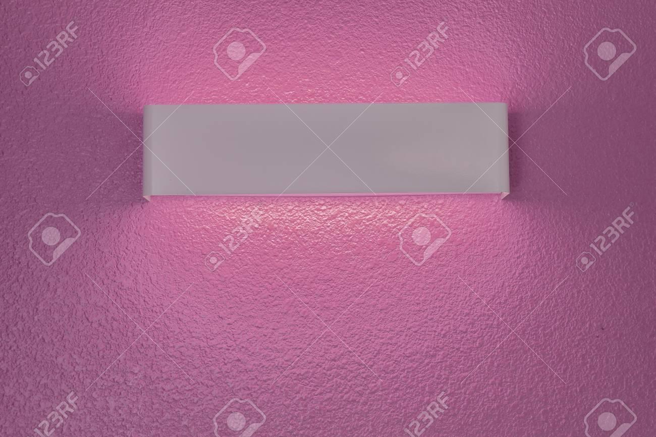 Applique moderna con paralume sul muro di cemento rosa foto royalty