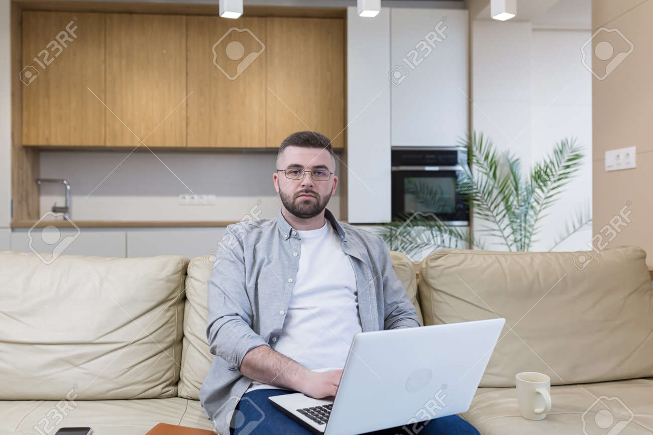 respectable handsome man working from home office, sitting on sofa with laptop, and solving business case - 166254924