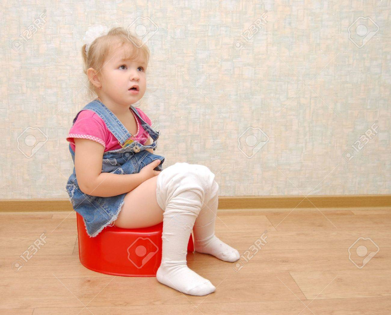 Potty girl Pretty girl/b and red potty/b on wooden floor (toilet)