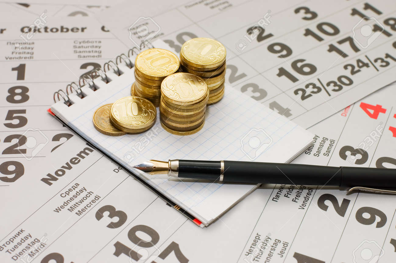 Sheets of a calendar with coins and a notebook Stock Photo - 8075637