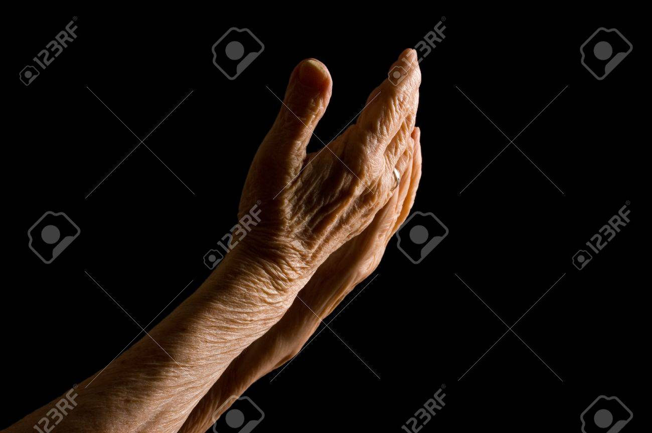 Hands of the old woman on a black background Stock Photo - 9035601
