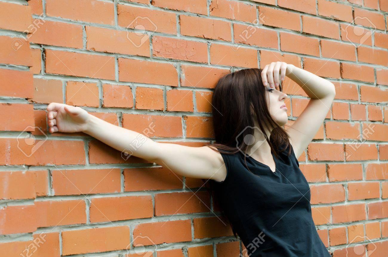 The young sad girl at brick walls Stock Photo - 10225483