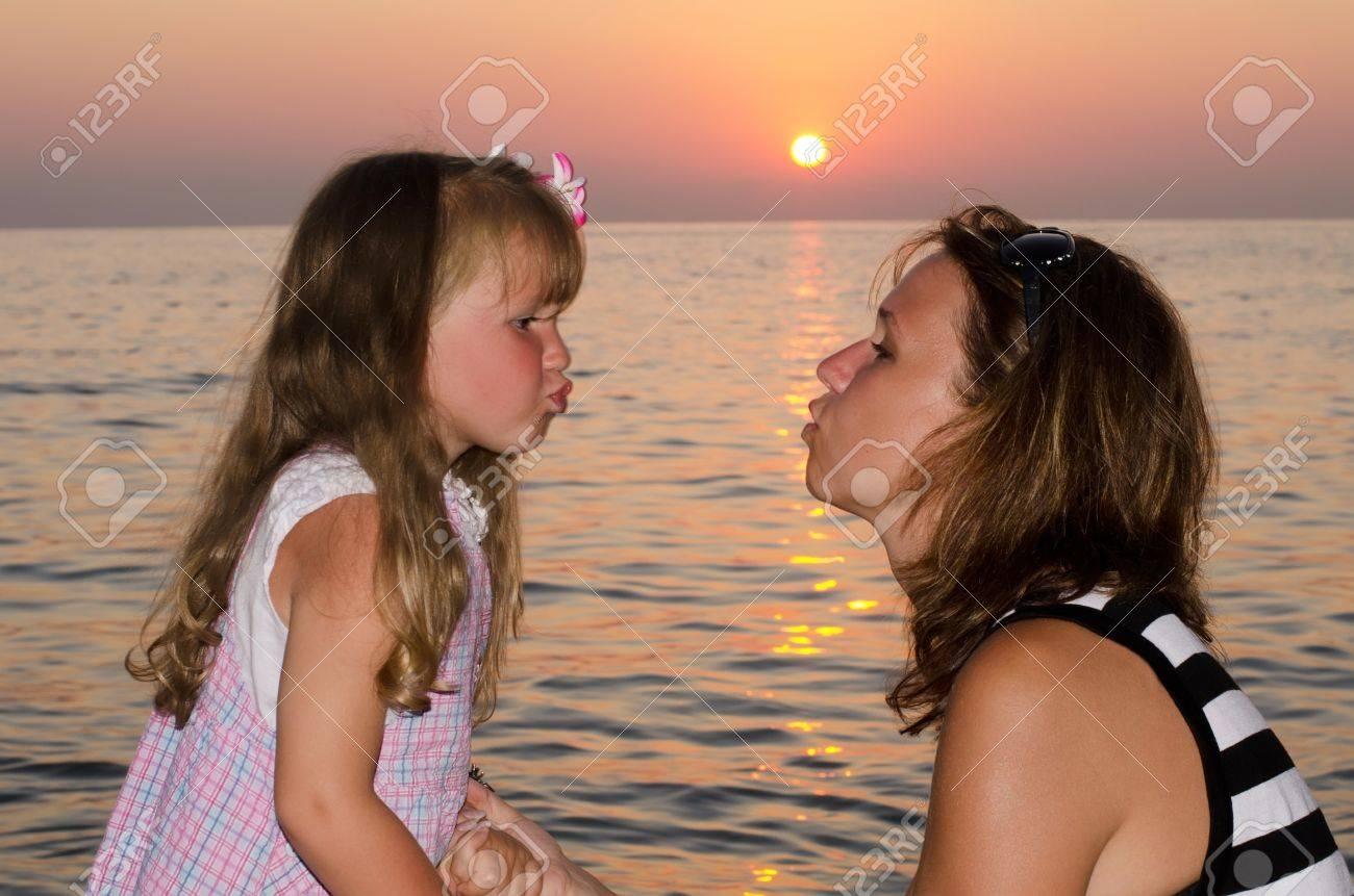 Mum a daughter kiss against a decline Stock Photo - 11708850