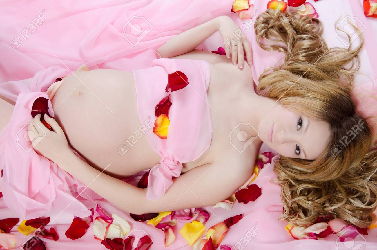 The pregnant woman On a pink coverlet Stock Photo - 12457109