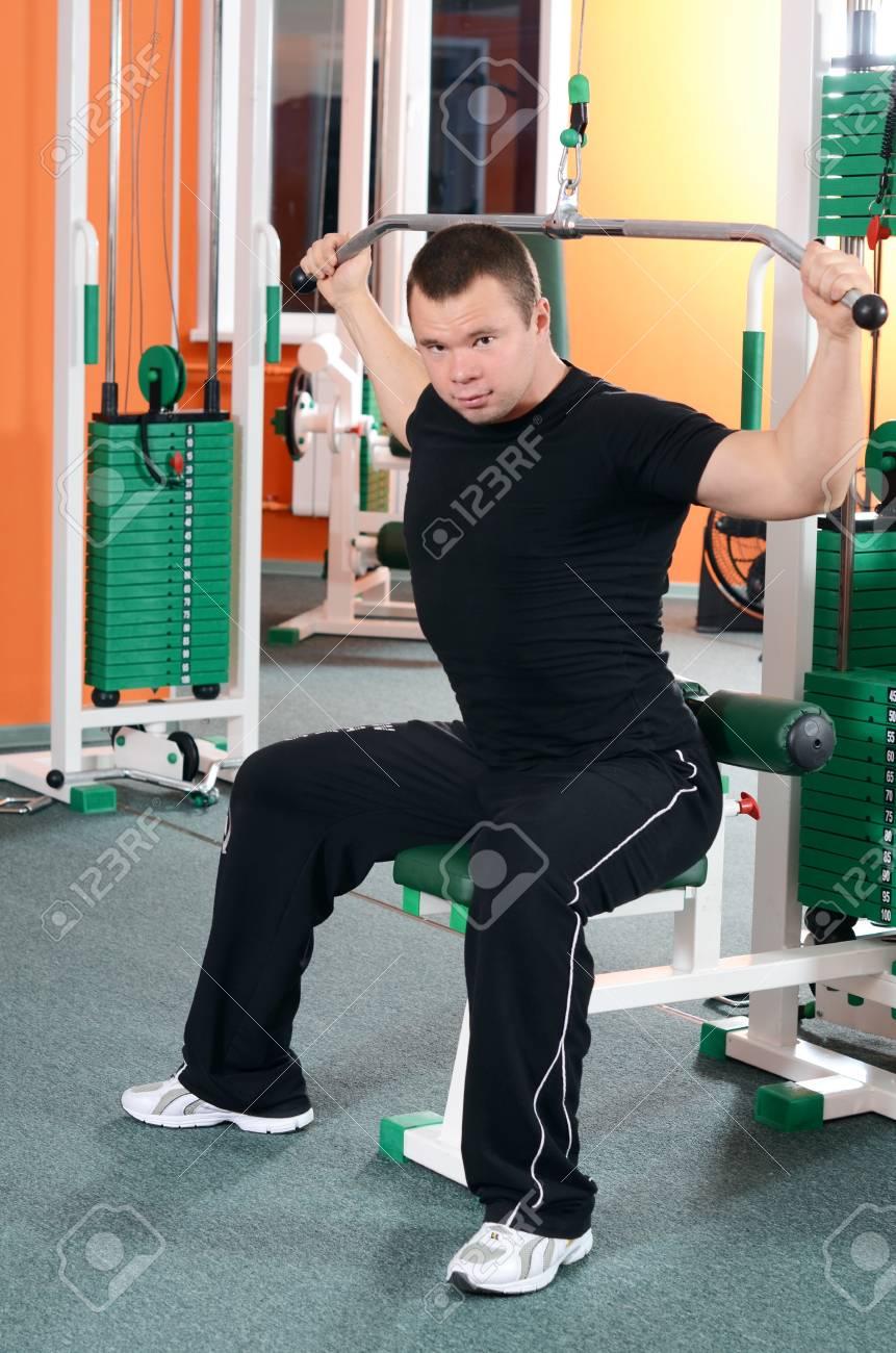 Man on training apparatus in sports club Stock Photo - 18558875