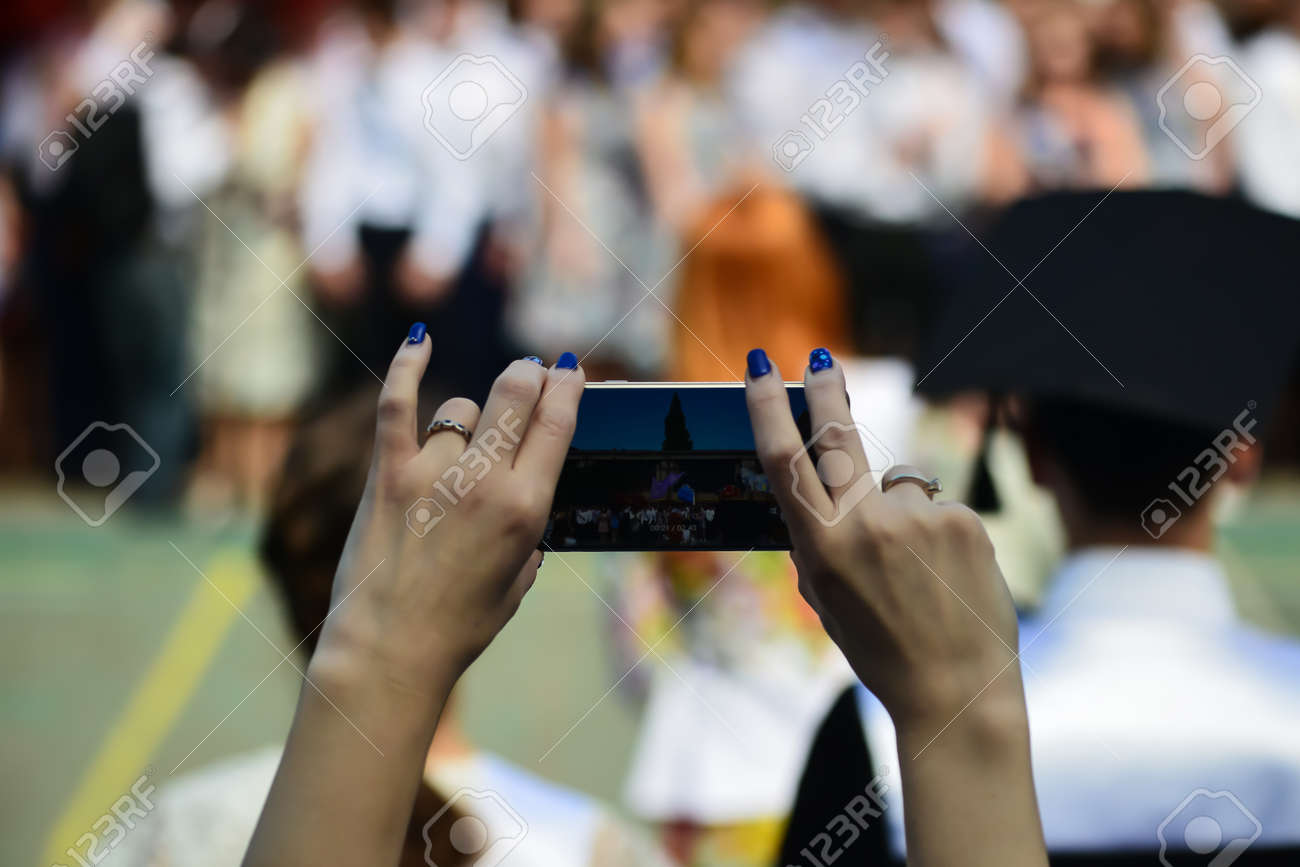 Woman using smartphone taking picture at graduation party. - 155722506