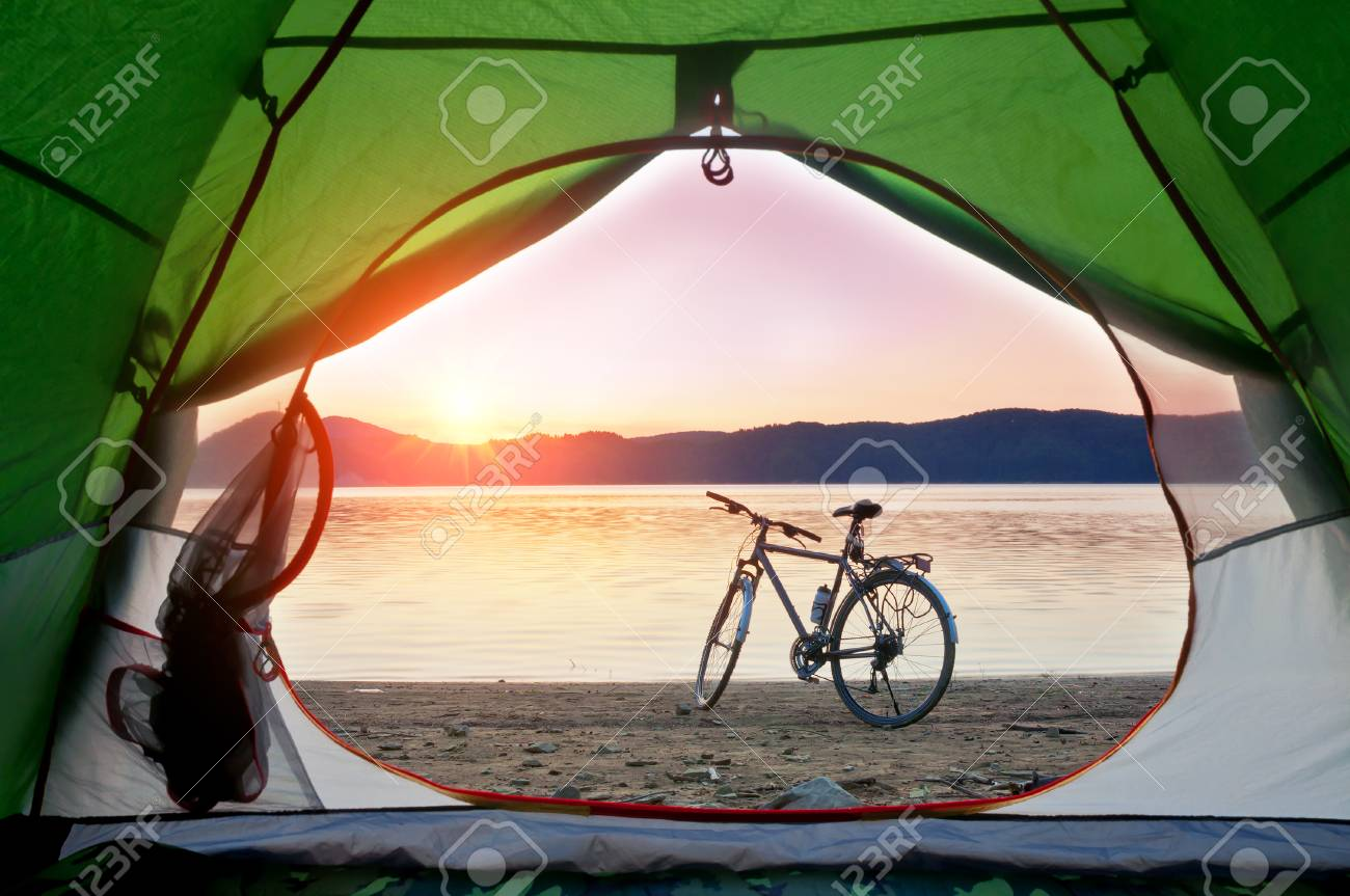 view from the tent to the lake with bicycle on sunset - 70035817