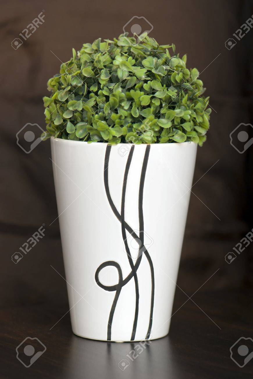Decorative flower in a narrow and tall ceramic planter. - 18014586