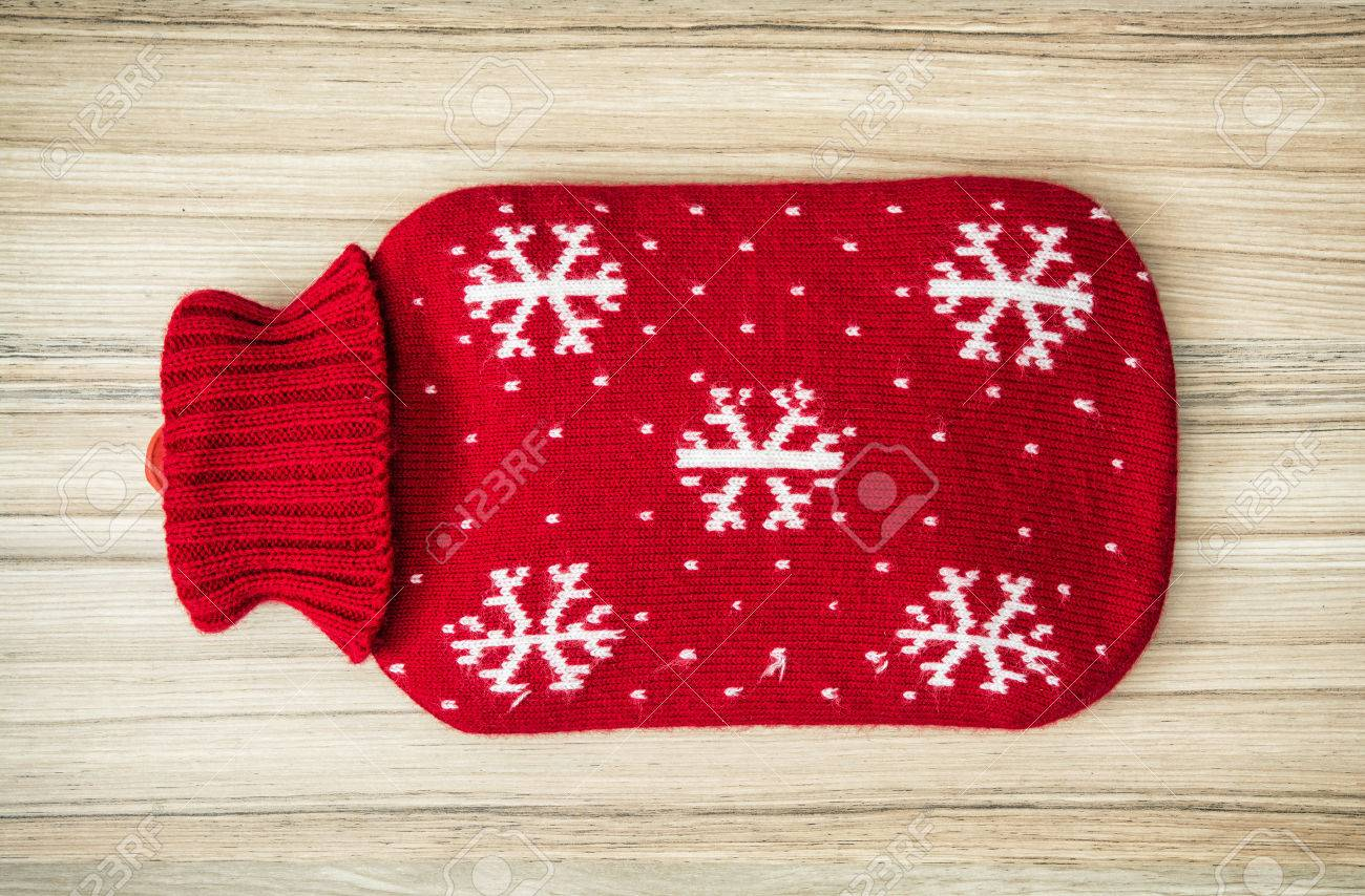 Red hot water bottle on the wooden background. - 50086591