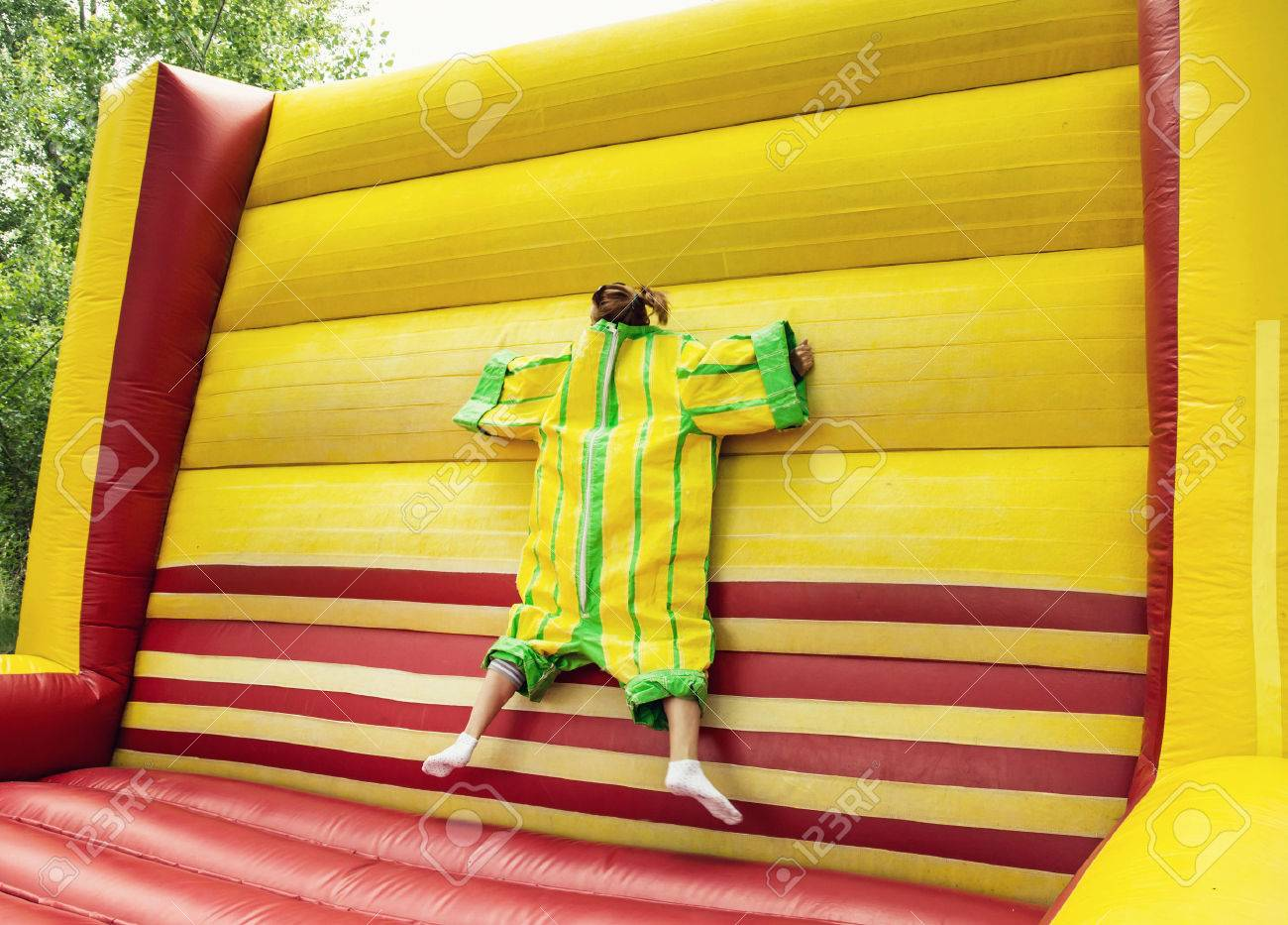 Young woman in plastic dress in a bouncy castle imitates a fly on velcro wall. Inflatable attraction. Leisure activity. - 53541227