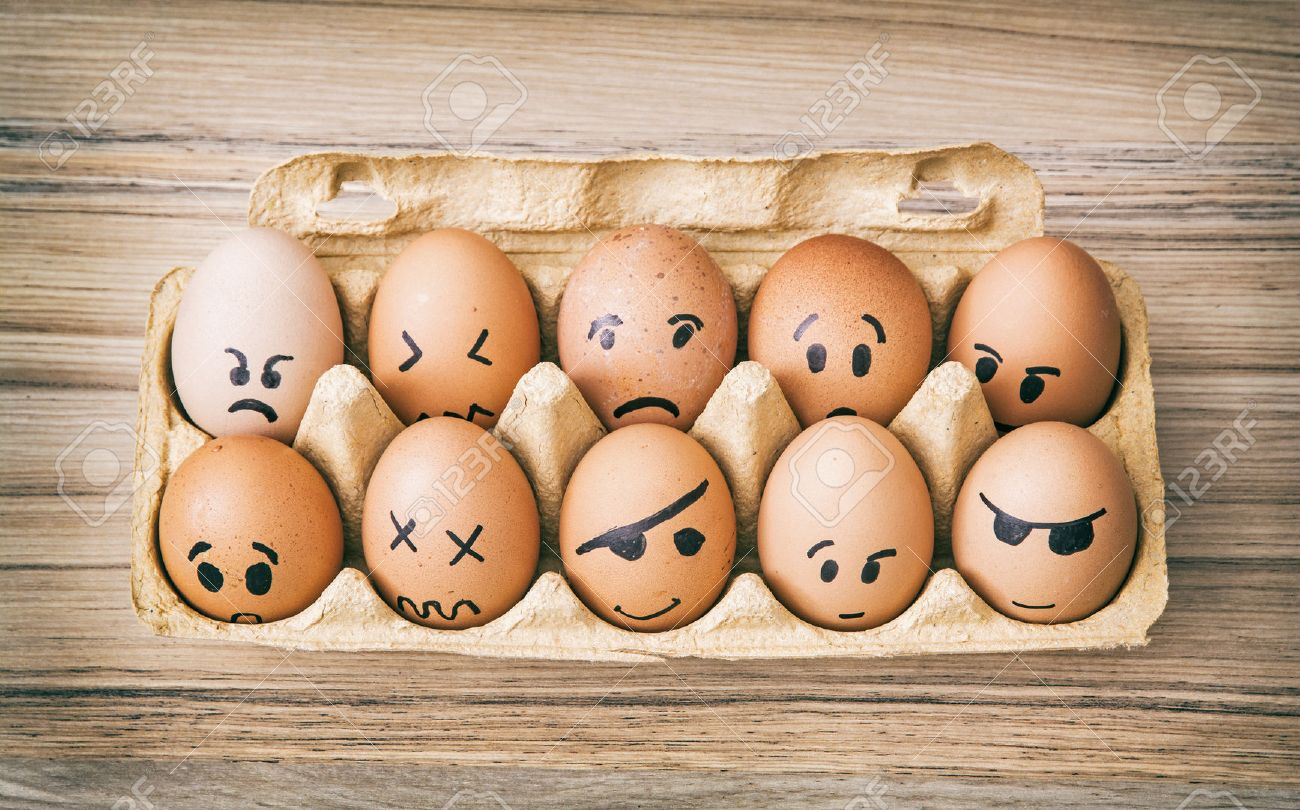 Emotion face painted eggs in paper box. Funny drawing faces. - 53541412