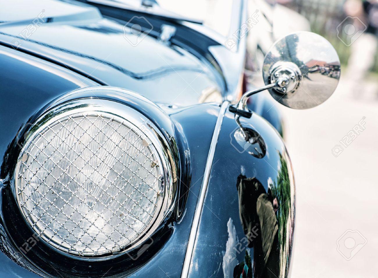 Shiny blue vintage car. Detail view of the headlight. Retro car. Front light. Retro automobile scene. Circle headlamp. - 58033487