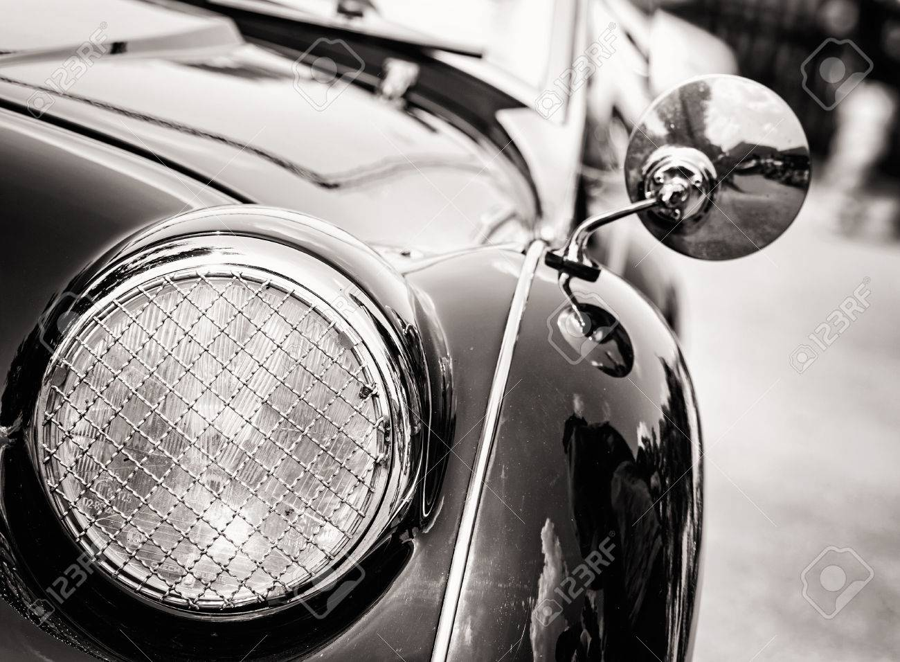 Shiny vintage car. Detail view of the headlight. Retro car. Black and white photo. Front light. Retro automobile scene. Circle headlamp. - 58033845