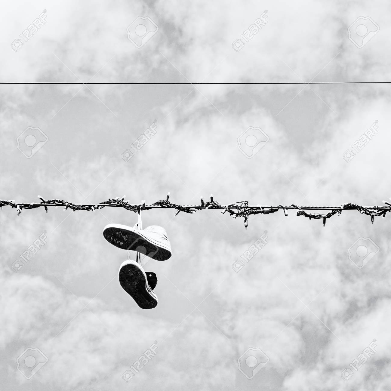 Sneakers hanging on the power line black and white photo bad joke stock