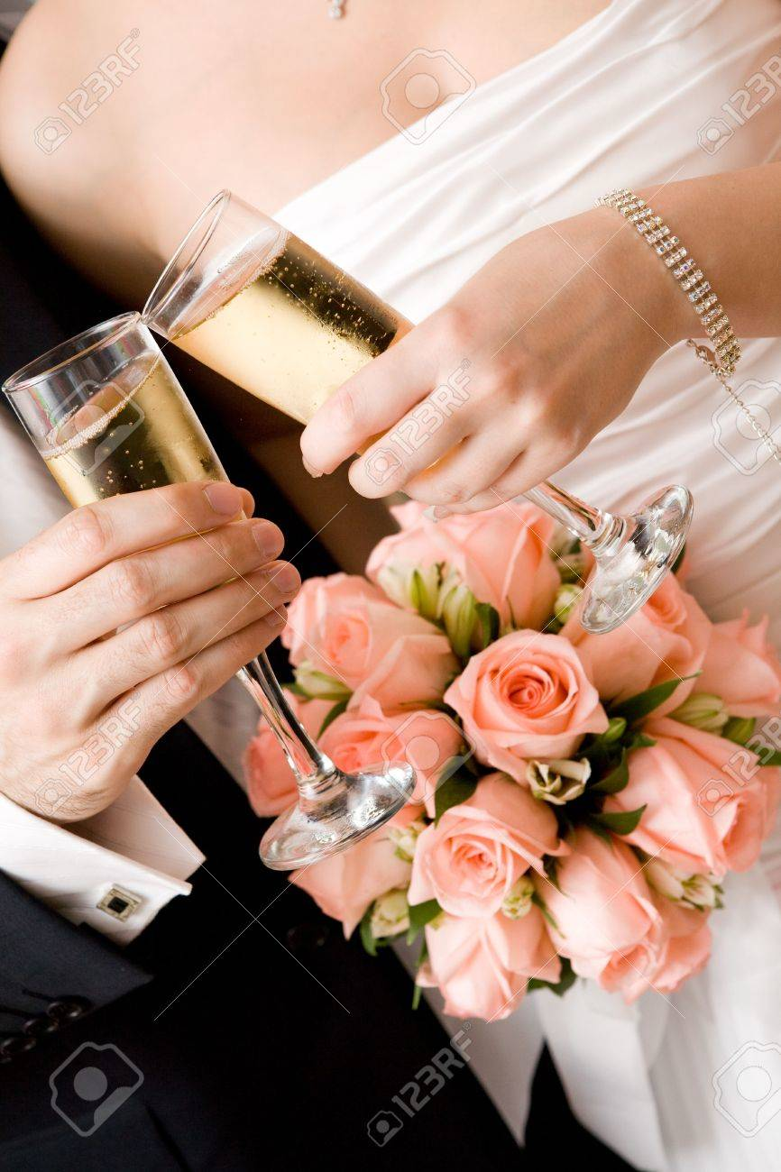 bride and groom with glasses of champagne and red rose bouquet Stock Photo - 3395829