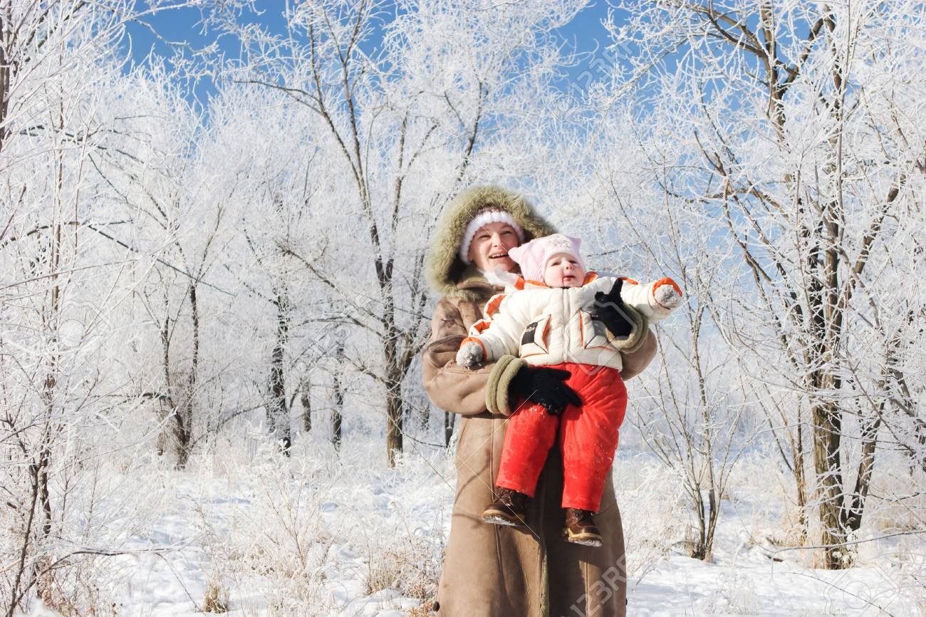 a mother and a child in a snow-covered winter forest looking up Stock Photo - 3808974