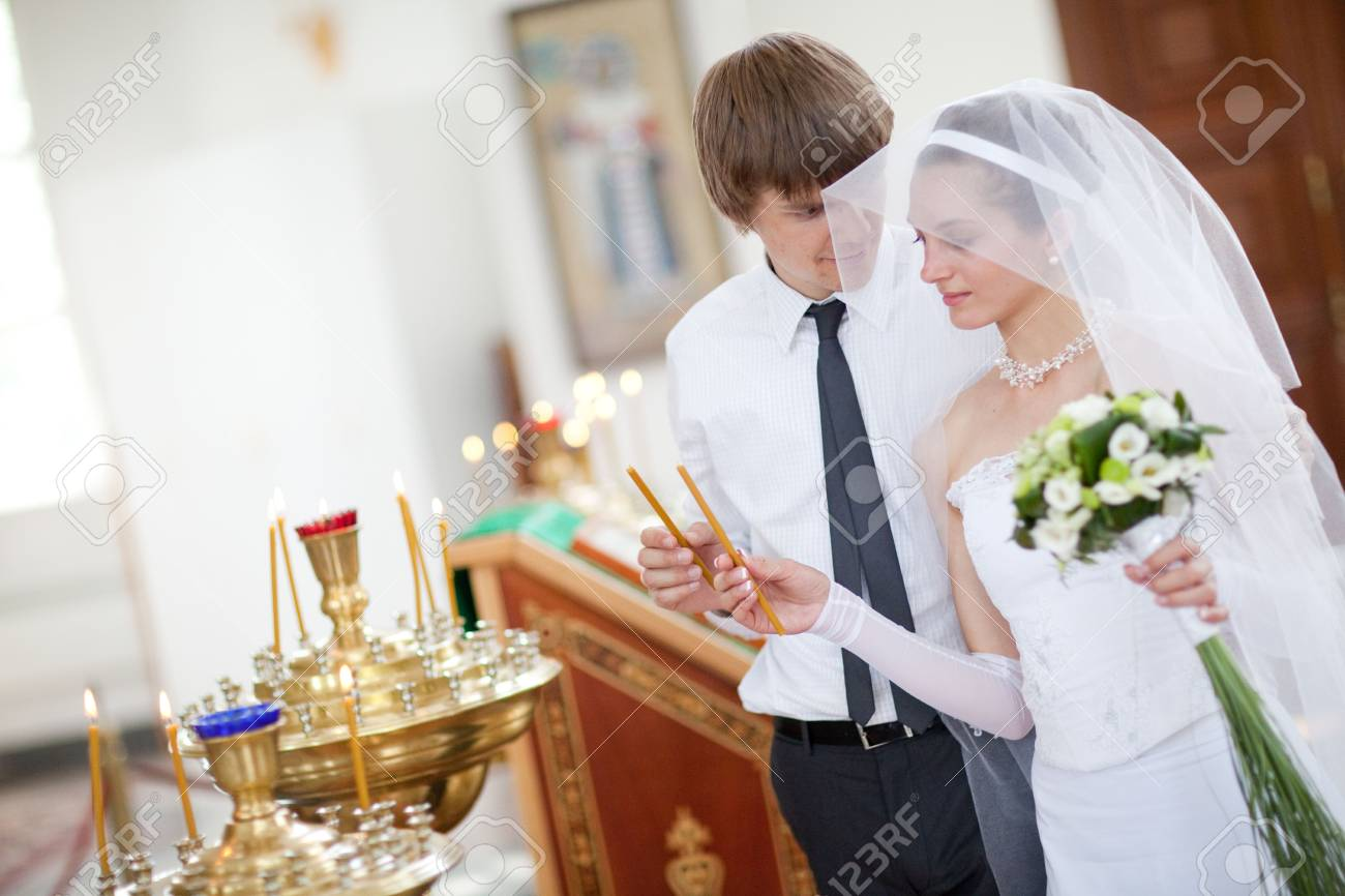 couple lighting candles in a church Stock Photo - 5687217