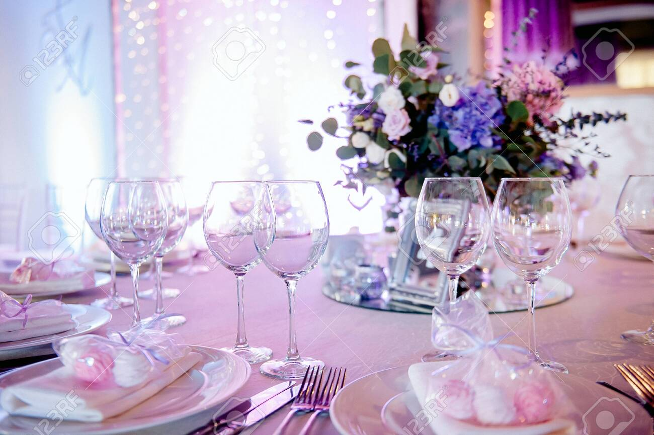 beautiful decor and festive table setting, illuminated by the light of multi-colored bulbs - 129920542