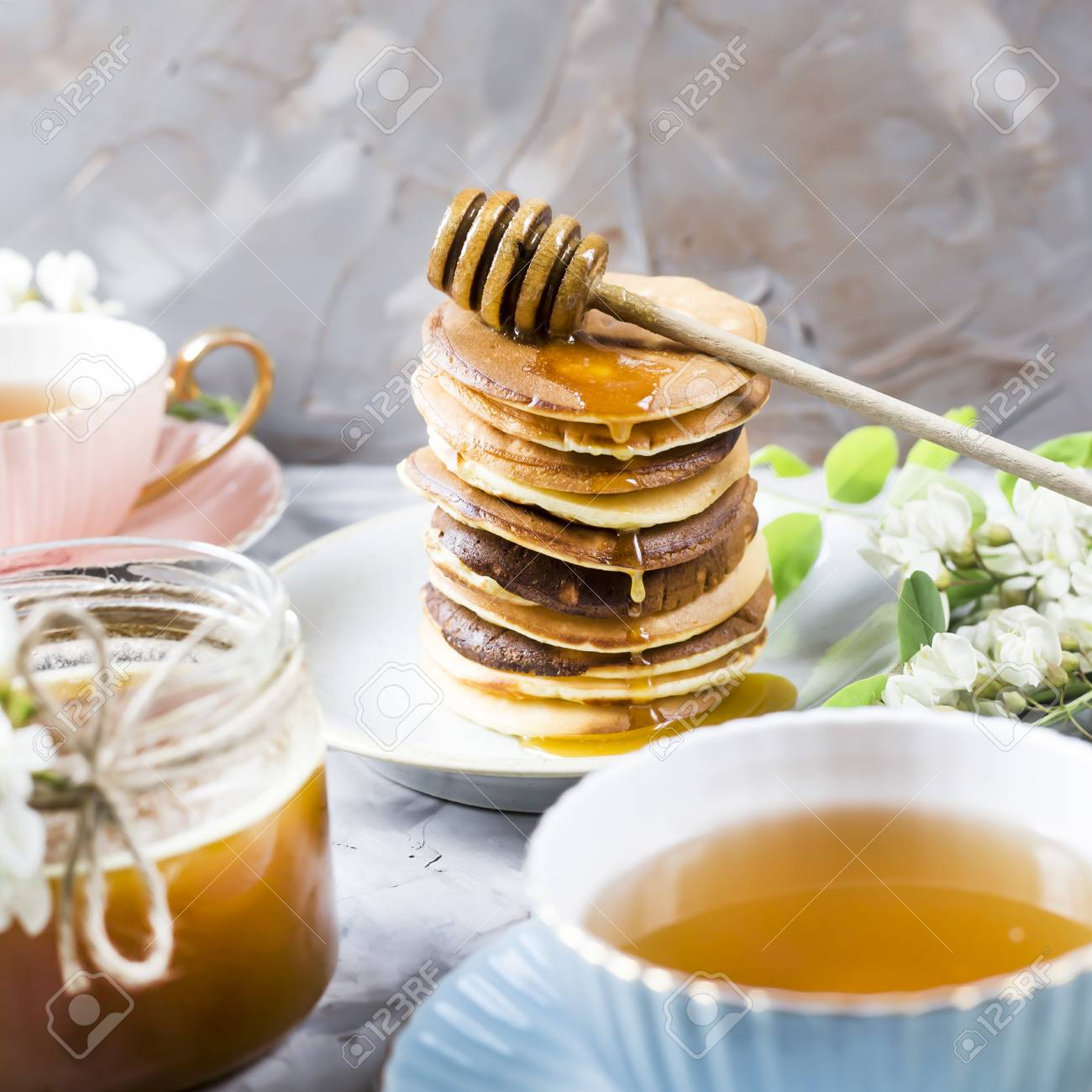 A Pile Of Fritters Next To A Cup Of Tea And A Jar Of Honey On