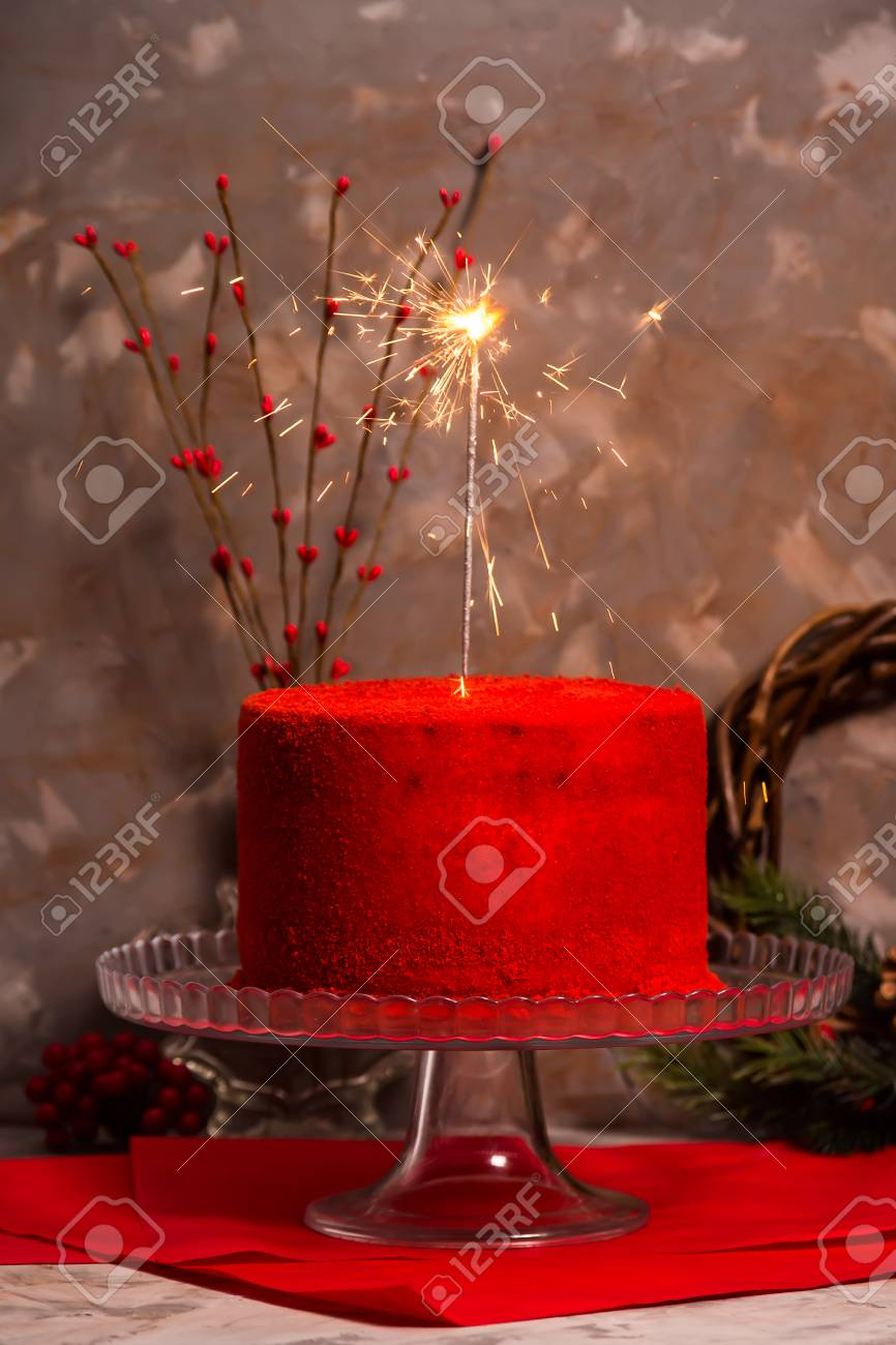 Bengal fire burning on a beautiful red velvet birthday cake on
