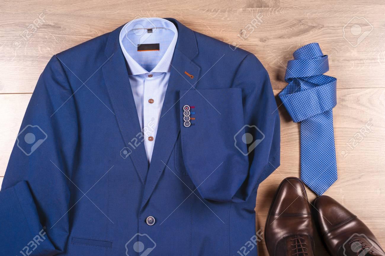 meilleur service eb549 a1409 Ensemble de vêtements pour hommes classiques - costume bleu, chemises,  chaussures marron, ceinture et cravate sur fond en bois.