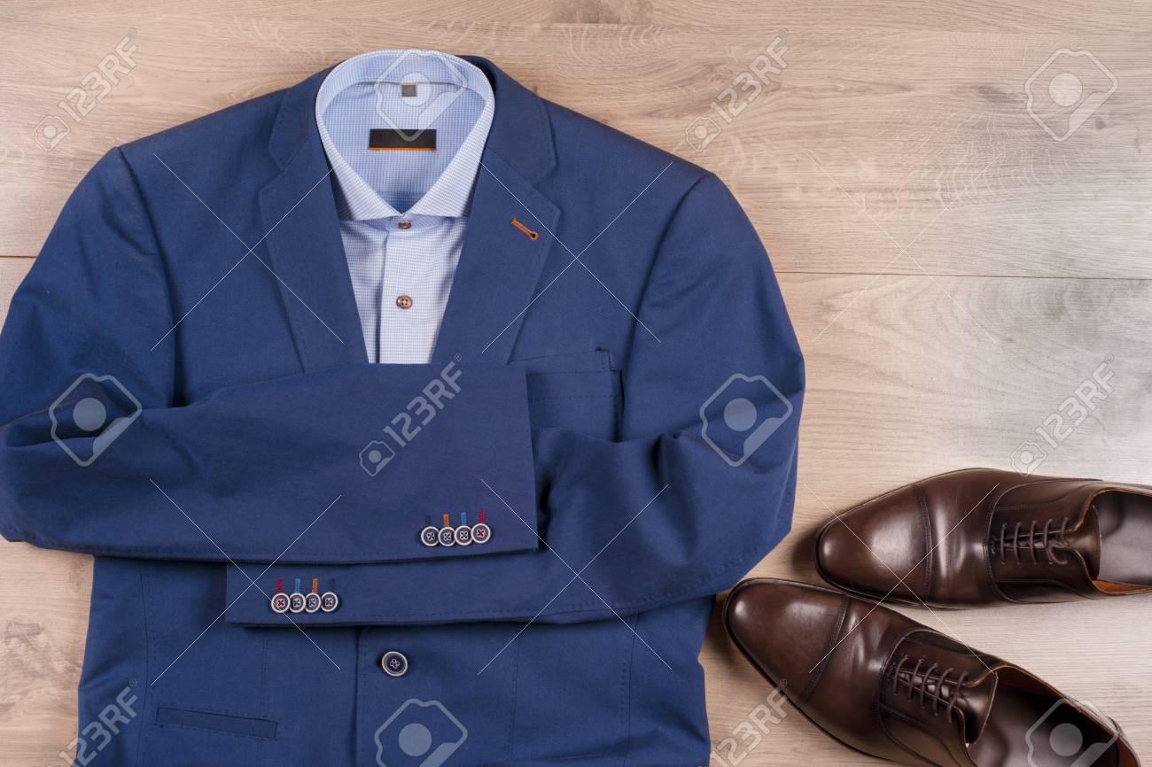 set of classic mens clothes , blue suit, shirts, brown shoes,..