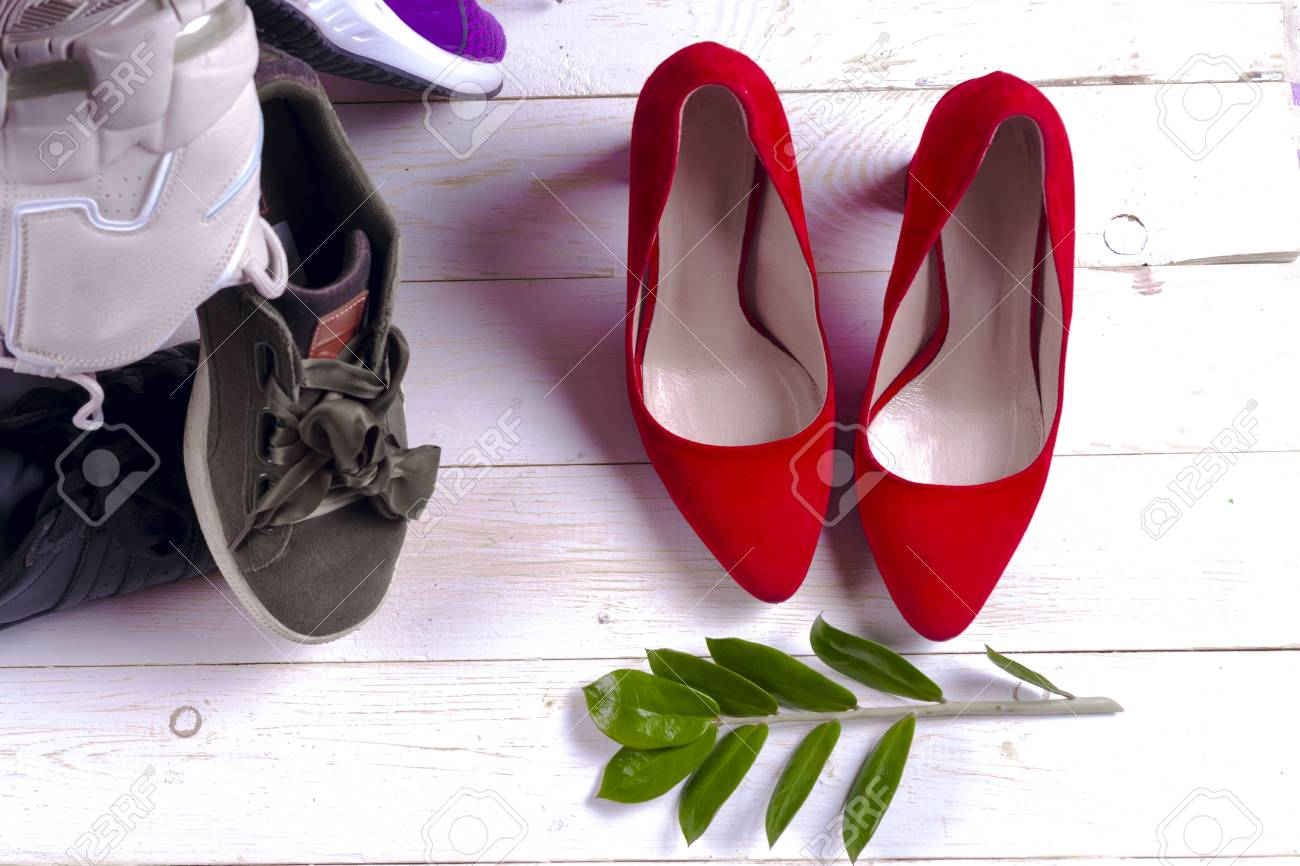 98b2ef608a38 Big heap of different sports shoes and red high heel womens shoes on white  background.