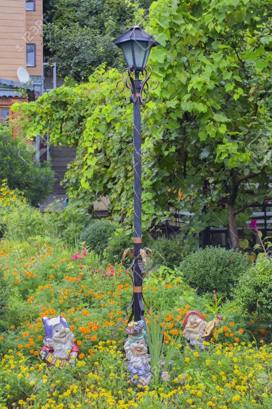 Exemple de décoration de jardin: lampe de rue et figurines de nains dans un  décor de jardin