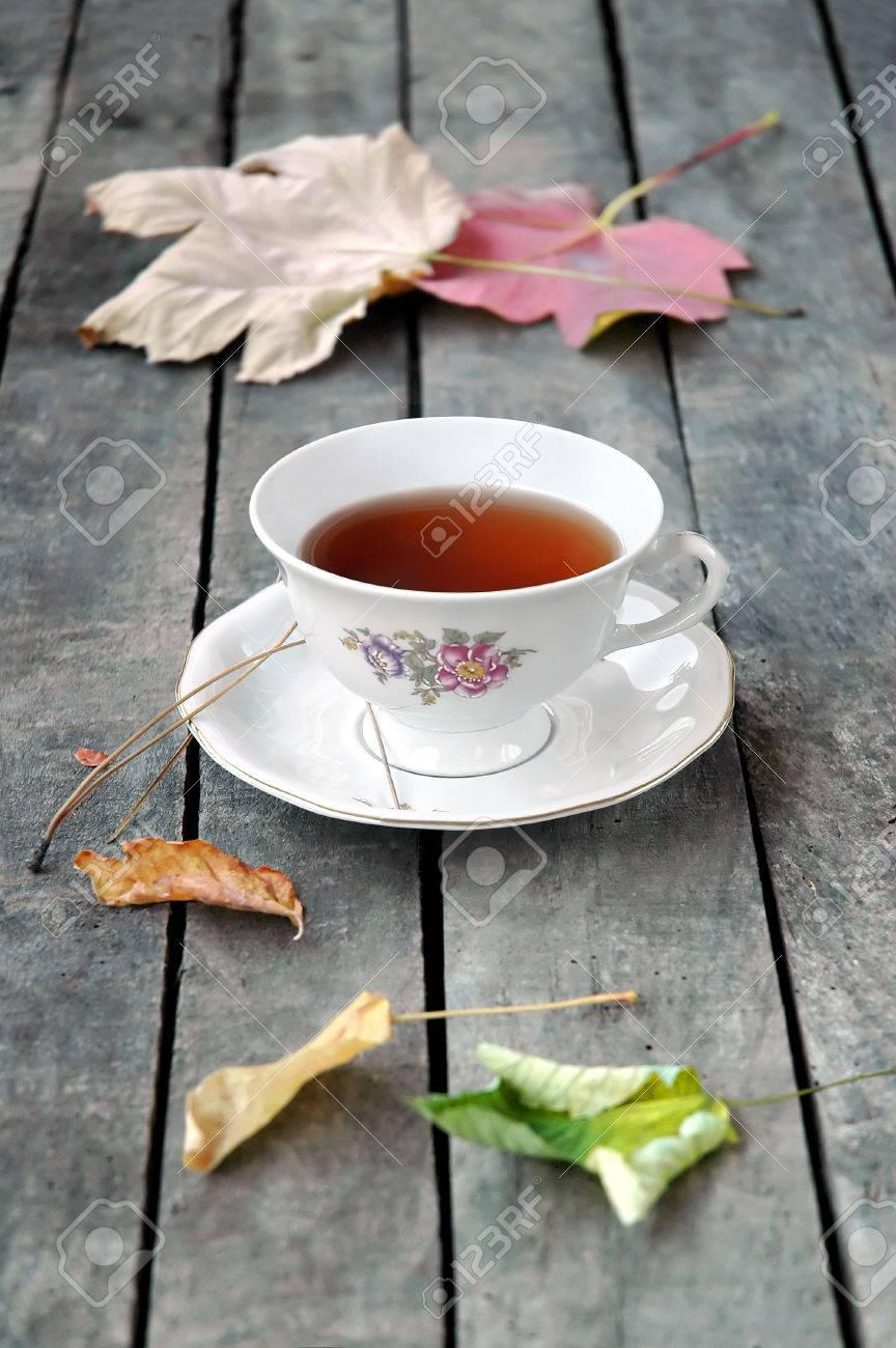White vintage cup of tea on grey rustic wooden table, with autumn leaves Stock Photo - 22606207