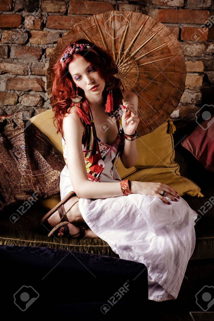 red hair woman sitting on sofa holding japanese parasol Stock Photo - 5017432