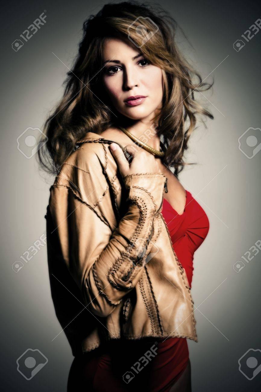 brunette woman taking off leather jacket, vertical orientation, studio shot Stock Photo - 8005303