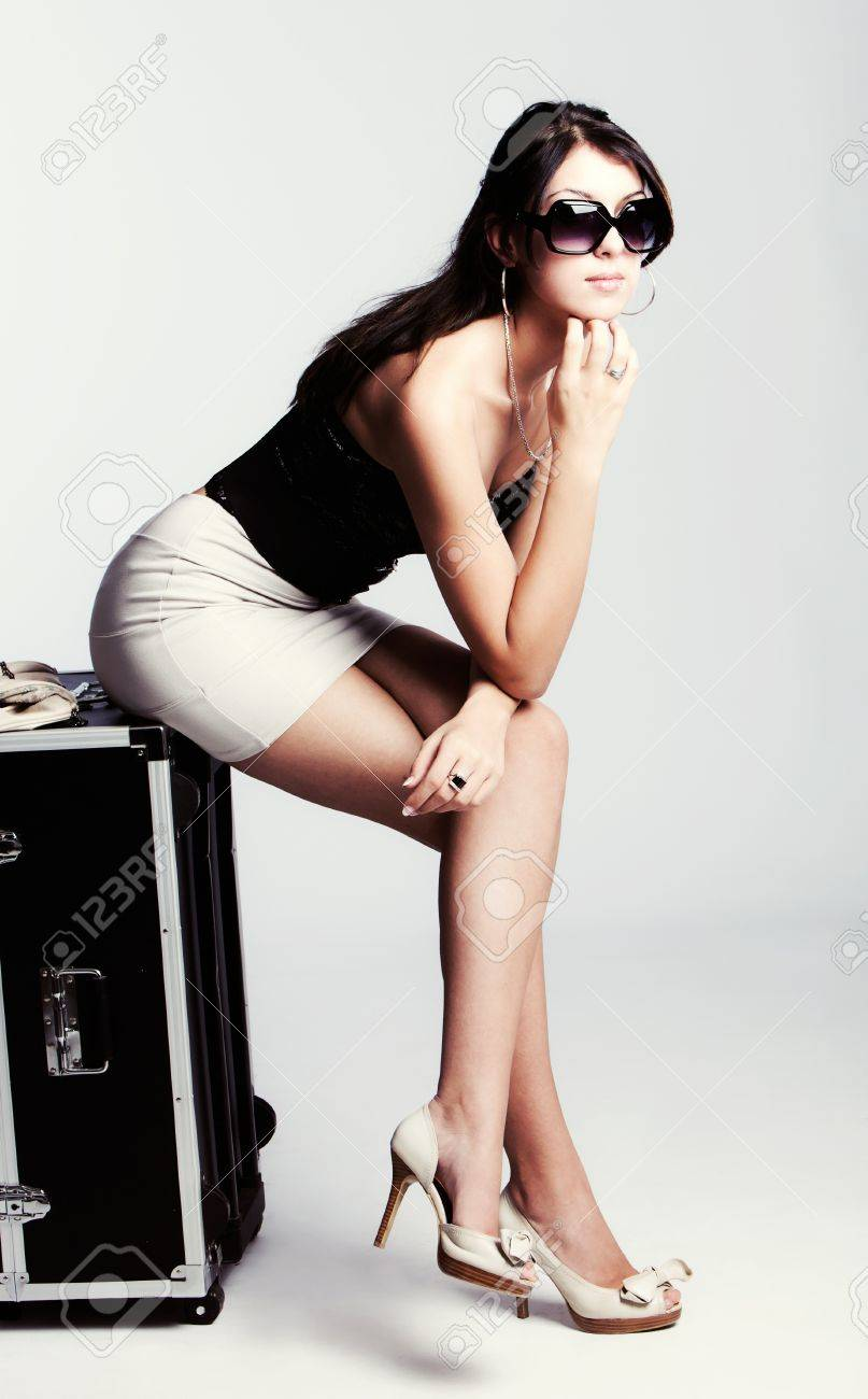 young woman in summer clothes sittting on luggage, studio shot, full body shot Stock Photo - 8816572