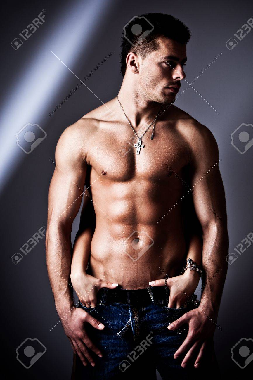 shirtless wet muscular man in jeans and woman hands, studio shot Stock Photo - 9103390