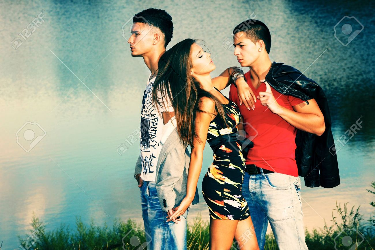 love triangle, two young men and young woman on the beach at sunset - 10689135