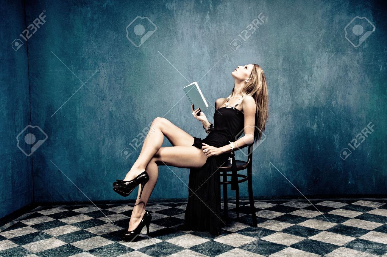 sensual blond in black dress and high heels sit on chair holding a book in empty room Stock Photo - 11111414