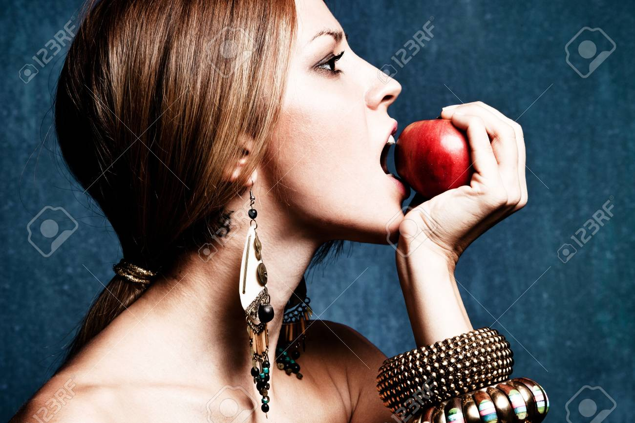 woman bite an apple, profile, studio shot Stock Photo - 11313785