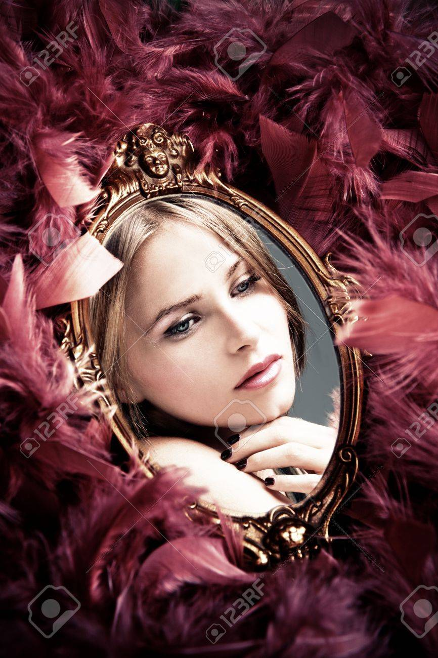 beautiful young woman reflection in mirror surrounded by plumage Stock Photo - 11687836