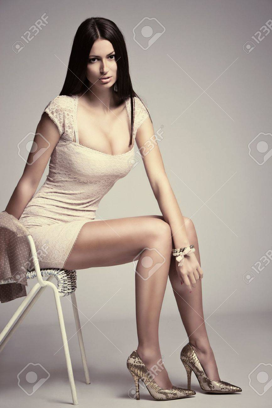 elegant young woman in short dress, high heels, sit on chair, studio shot, small amount of grain added Stock Photo - 12406642