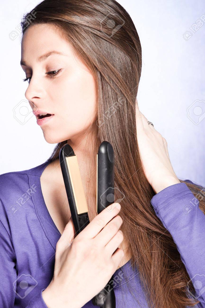 young brunette woman use hair straightener iron, studio shot Stock Photo - 13197944
