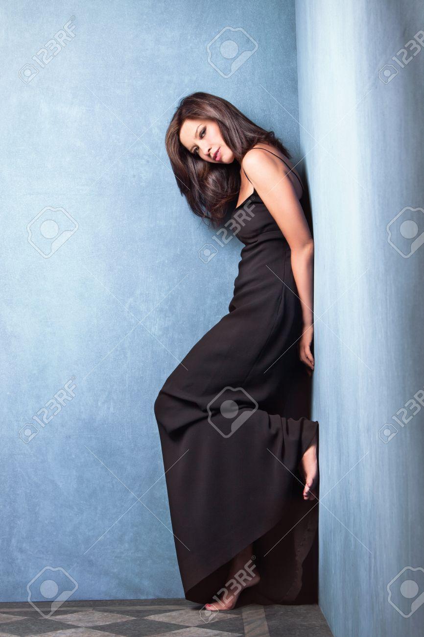 mature beautiful woman in long elegant black dress stand in corner