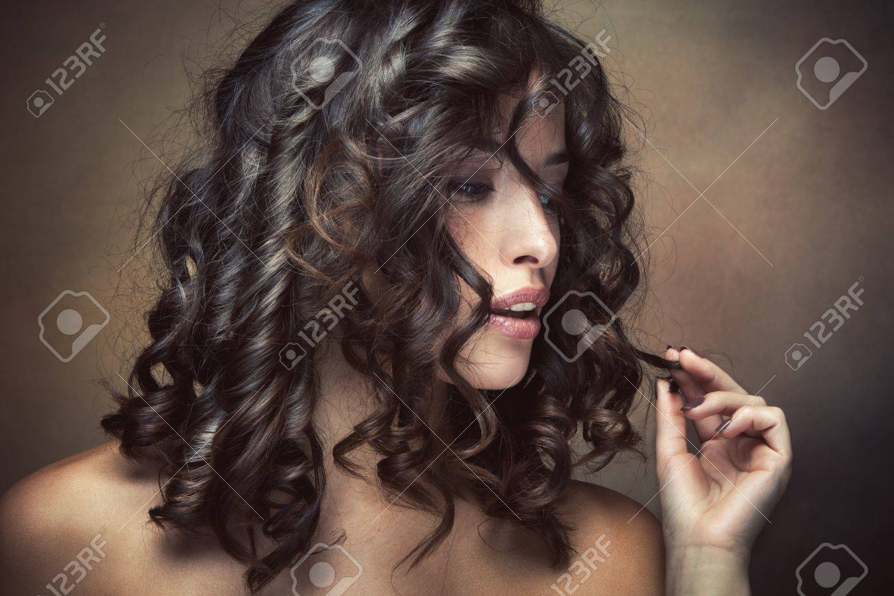sensual brunette woman with shiny curly silky hair studio shot Standard-Bild - 15175447