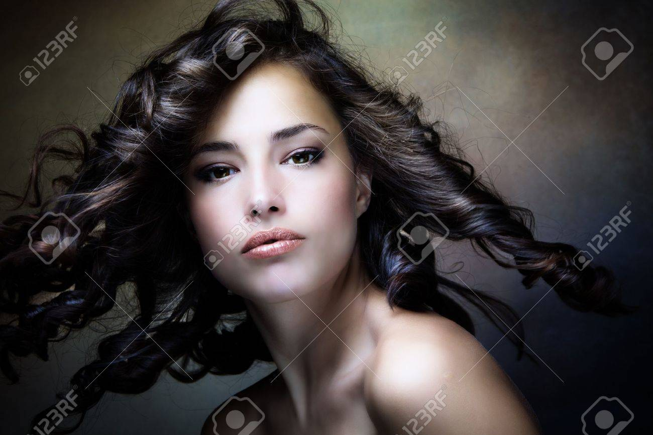 sensual brunette woman with shiny curly silky hair in motion studio shot Stock Photo - 16216556