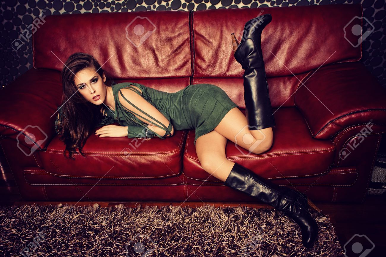 young fashion female model in short green dress and high heel boots pose on red leather sofa Standard-Bild - 17577026