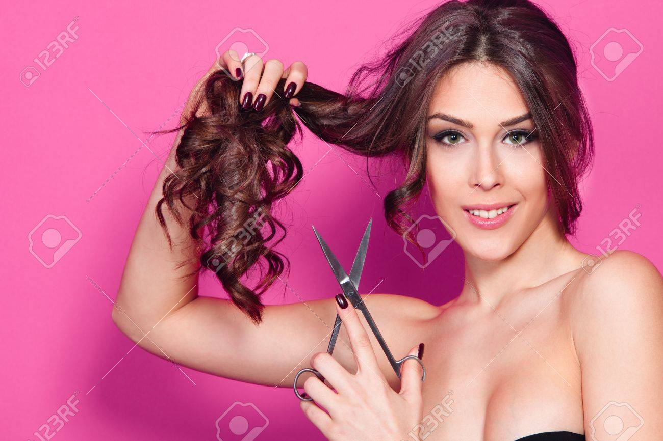 young woman hold scissors studio shot pink background Standard-Bild - 18634013