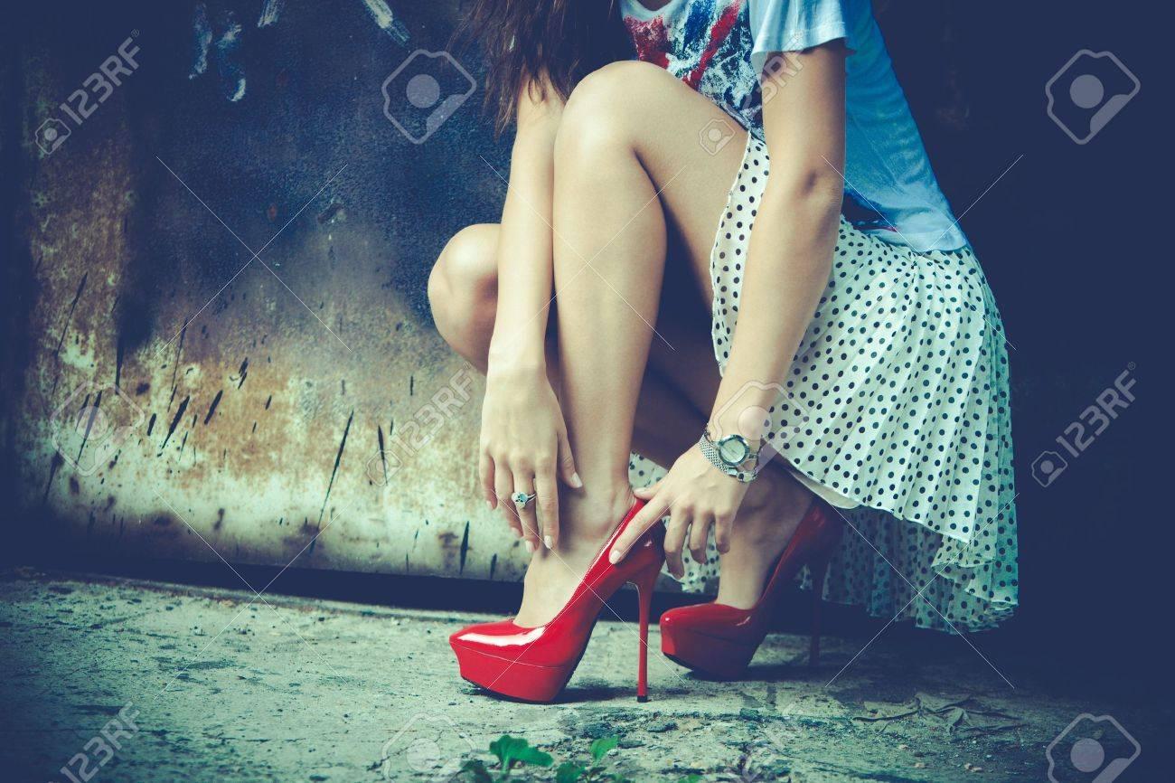 woman legs in red high heel shoes and short skirt outdoor shot against old metal door Standard-Bild - 20886887
