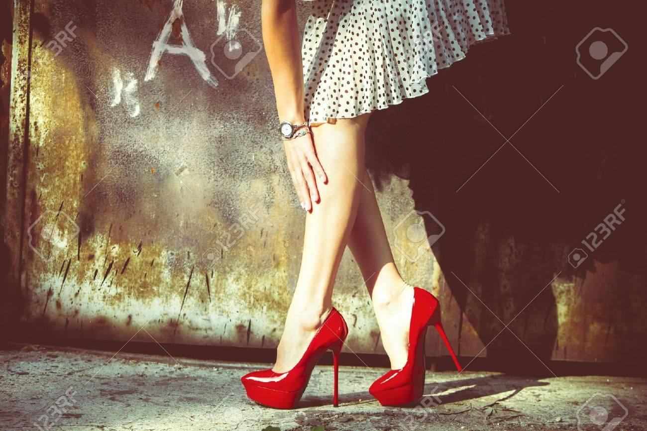 fdb44f4fc Jambes de la femme dans les chaussures rouges à talons hauts et jupe courte  tir en plein air contre la porte du vieux métal