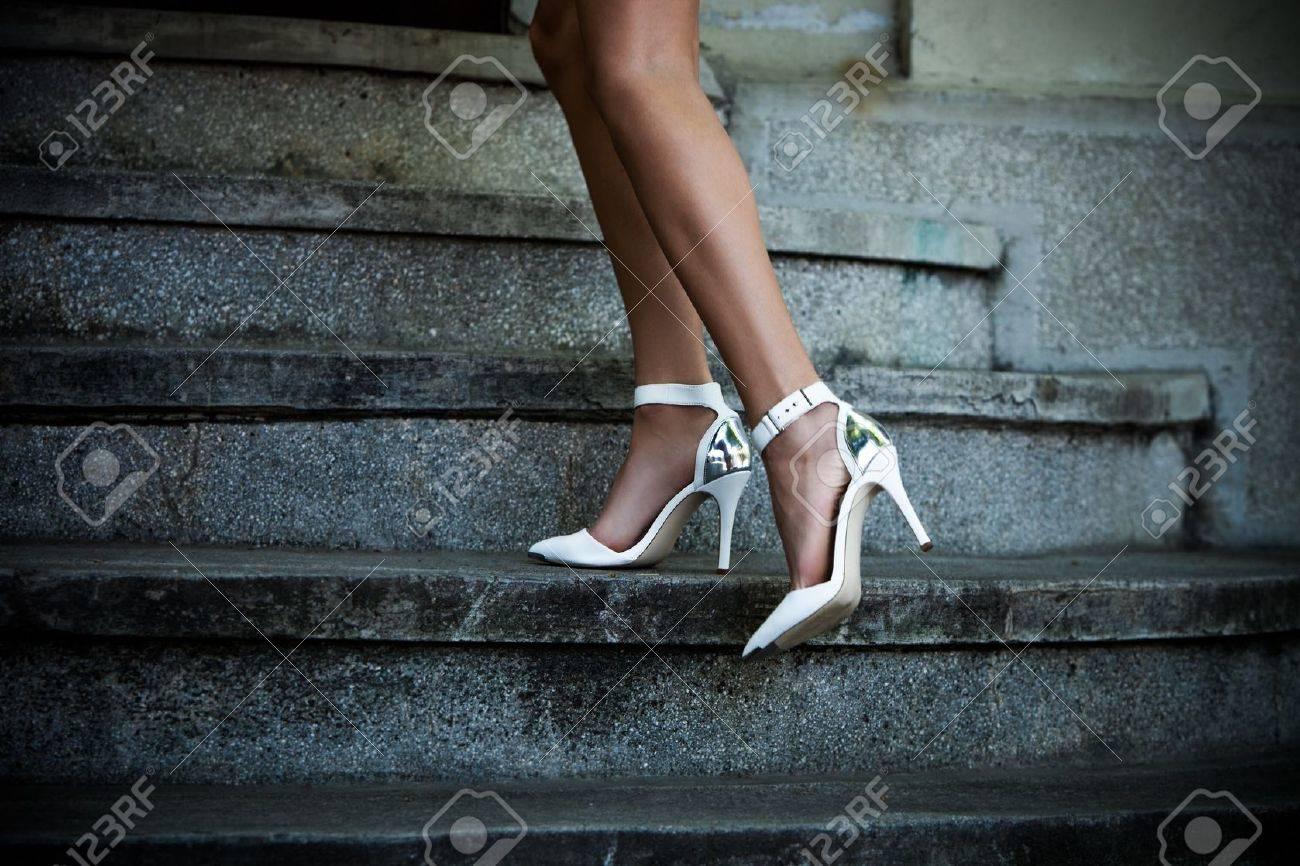 Piernas de la mujer en las escaleras en elegantes zapatos blancos de tacón día de verano al aire libre disparo