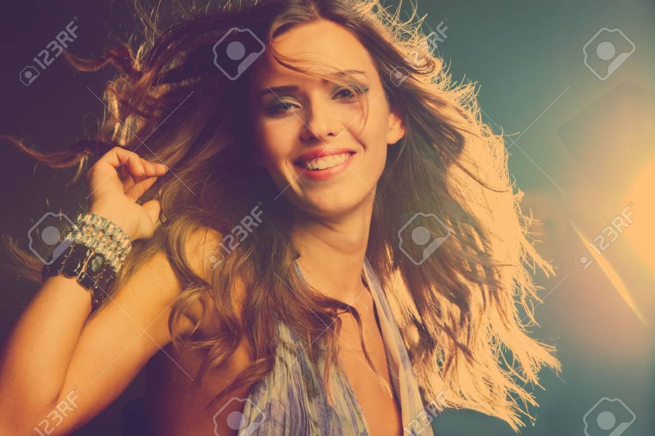 smiling young girl dancing in night club, retro colors Standard-Bild - 24000569